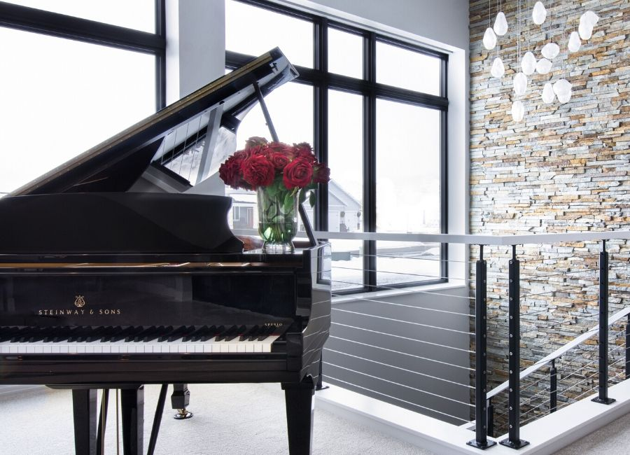 Grand Piano against large windows and stone veneer wall